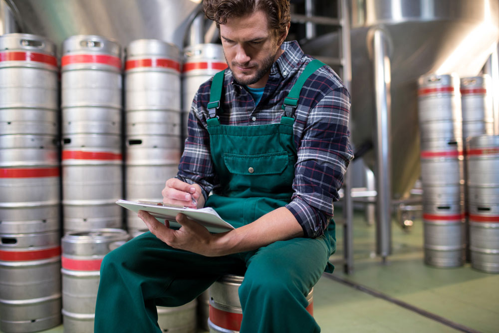 Brewery worker checking paperwork